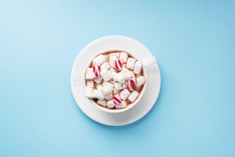 Puchar gorącej czekolady z pudłem z kakao i karmelem na pastelowo niebieskim tle z przestrzenią do kopiowania Koncepcja zimowa fotografia royalty free
