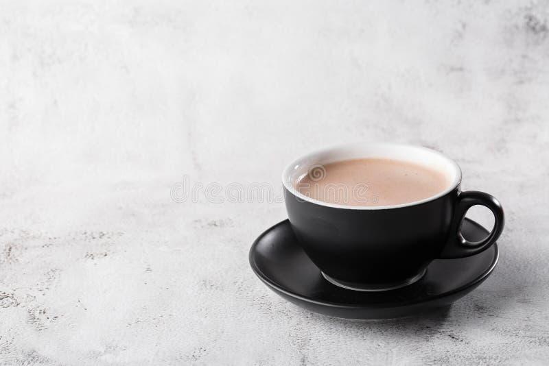 Puchar gorącej kakao lub gorącej czekolady w ciemnym kubku, odizolowany na jasnym marmurowym tle Widok ogólny, przestrzeń do kopi zdjęcie stock