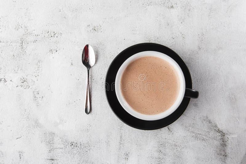 Puchar gorącej kakao lub gorącej czekolady w ciemnym kubku, odizolowany na jasnym marmurowym tle Widok ogólny, przestrzeń do kopi obraz stock