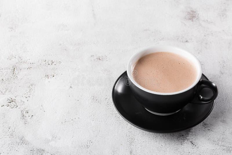 Puchar gorącej kakao lub gorącej czekolady w ciemnym kubku, odizolowany na jasnym marmurowym tle Widok ogólny, przestrzeń do kopi obrazy royalty free