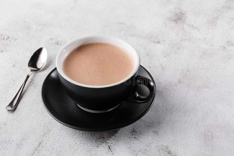 Puchar gorącej kakao lub gorącej czekolady w ciemnym kubku, odizolowany na jasnym marmurowym tle Widok ogólny, przestrzeń do kopi zdjęcie royalty free