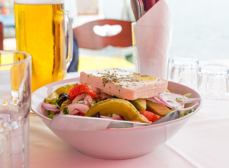 Puchar Grecka sałatka z feta serem, zielonym pieprzem, pomidorem, oliwkami i czerwoną cebulą, Piwny kubek i puści szkła na s obraz royalty free