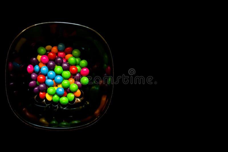 Puchar kolorowi cukierki na czarnym tle z kopii przestrzenią zdjęcia stock