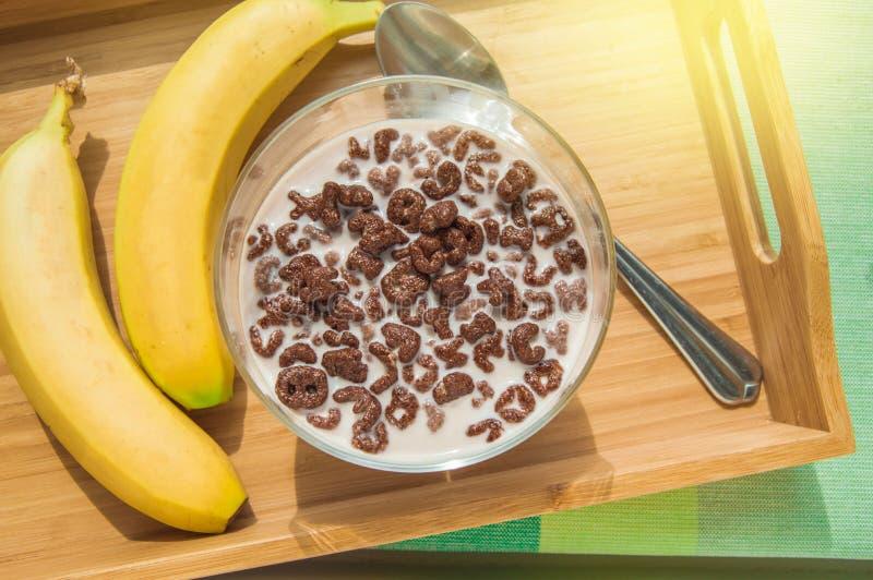 Puchar oatmeal czekoladowi p?atki w formie list?w abecad?o z mlekiem na drewnianej tacy z bananami, zdrowych obraz stock