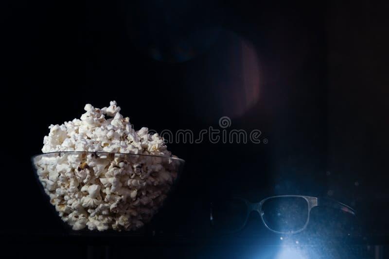 Puchar popkorn i 3d kinowi szkła w czarnym tle obrazy royalty free