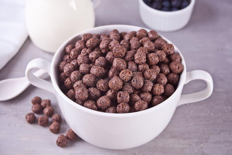 Puchar suche czekoladowe piłki zboże i butelka jeżeli mleko na szarość stole dla zdrowia śniadania fotografia stock