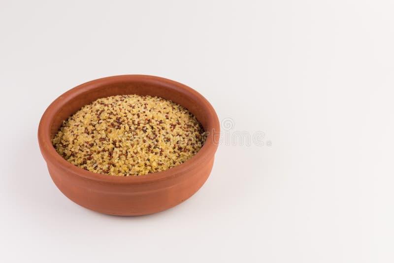Puchar surowy bulgur i quinoa odizolowywający na bielu zdjęcie stock