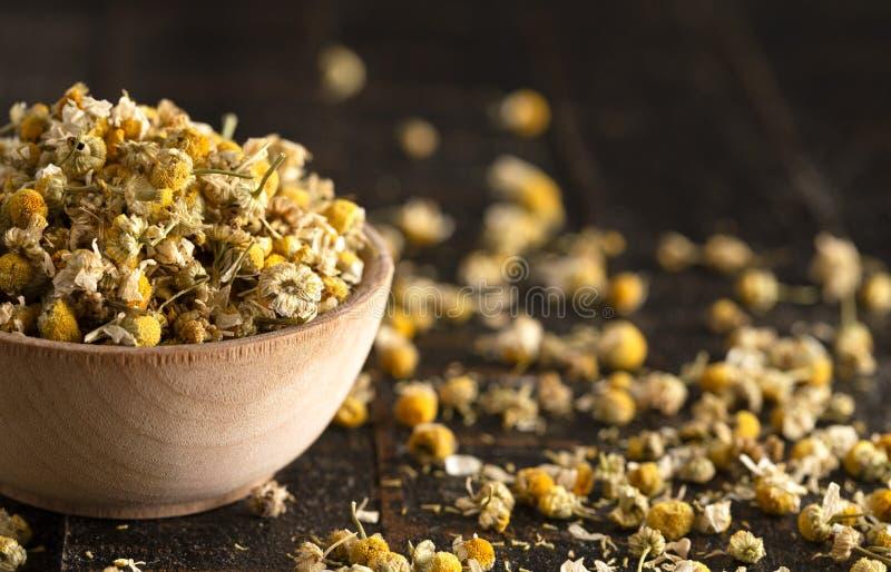 Puchar Wysuszeni Chamomile kwiaty Rozlewający na Ciemnym Drewnianym stole zdjęcia royalty free