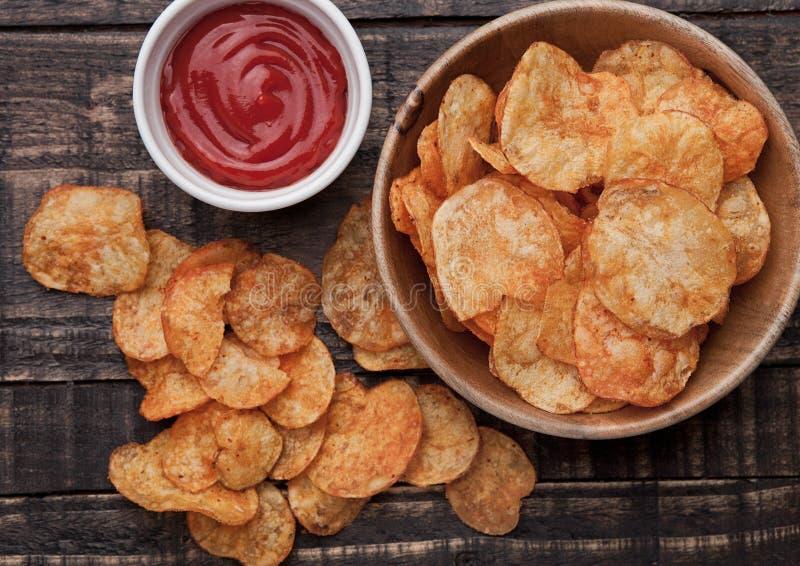 Puchar z kartoflanych chipsów ketchupem na drewnianej desce i układami scalonymi zdjęcia royalty free