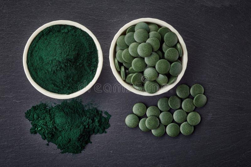 Puchary spirulina alg pastylki i proszek zdjęcia stock