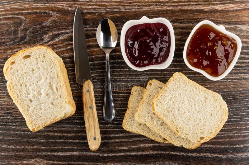 Puchary z morelowym dżemem, porzeczkowy dżem, łyżka, nóż, plasterki chleb na drewnianym stole Odg?rny widok obraz royalty free