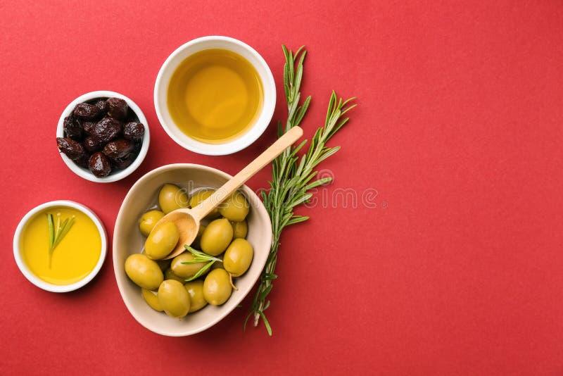 Puchary z oliwkami i olejem na koloru tle obrazy royalty free