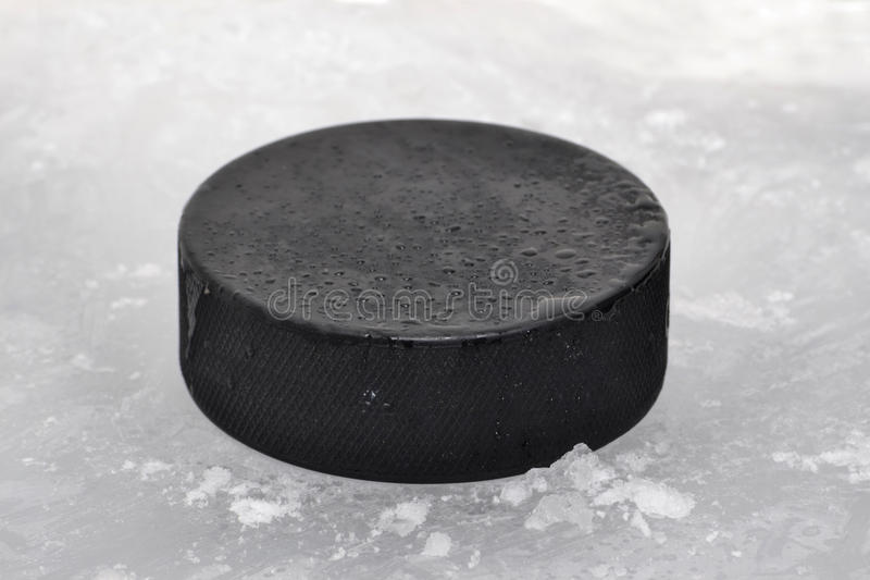Puck. A hockey puck on ice royalty free stock photo