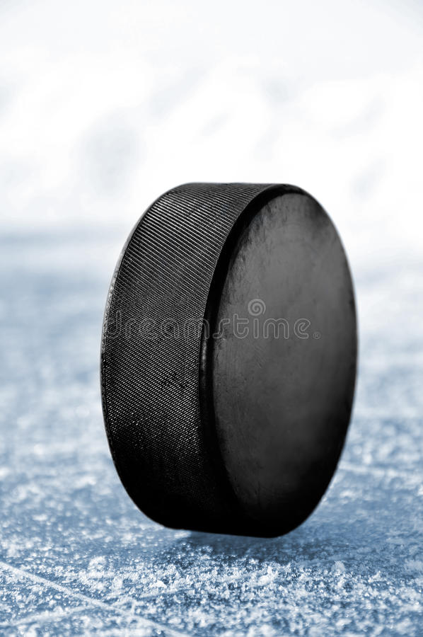 Puck. Black hockey puck on ice rink royalty free stock images