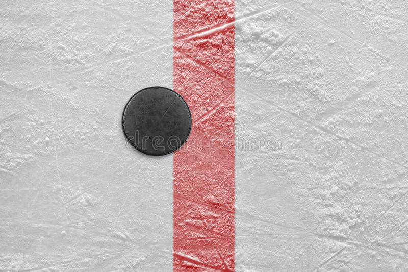 Puck on goal line. Puck lying on the red goal line. Texture, background royalty free stock photo