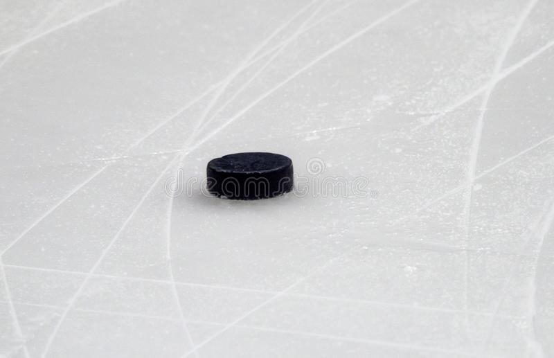 Puck on ice hockey rink surface, sport background.  royalty free stock photo