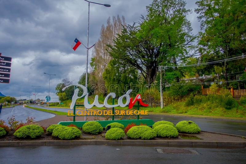 PUCON, CHILE - SEPTEMBER, 23, 2018: Informative wooden signs in a pole with a huge letters at the enter of the town in. The city in Pucon in Chile royalty free stock image