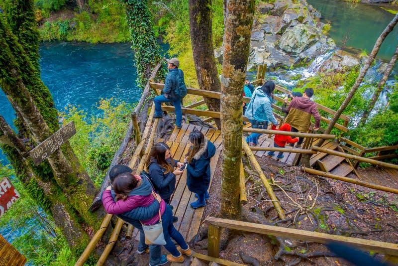 PUCON, CHILI - SEPTEMBER, 23, 2018: Boven mening van toeristen die dicht bij de watervallen met sommige houten omheiningen lopen  stock afbeelding
