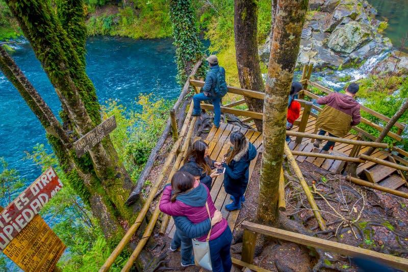 PUCON, CHILI - SEPTEMBER, 23, 2018: Boven mening van toeristen die dicht bij de watervallen met sommige houten omheiningen lopen  royalty-vrije stock fotografie