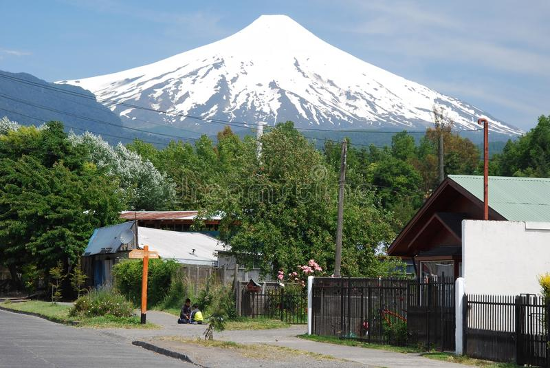 Pucon, overlooking the snowy volcano Villarrica from the city. Seen with children playing and houses, Chilean city located in the Province of Cautín, Araucan royalty free stock image