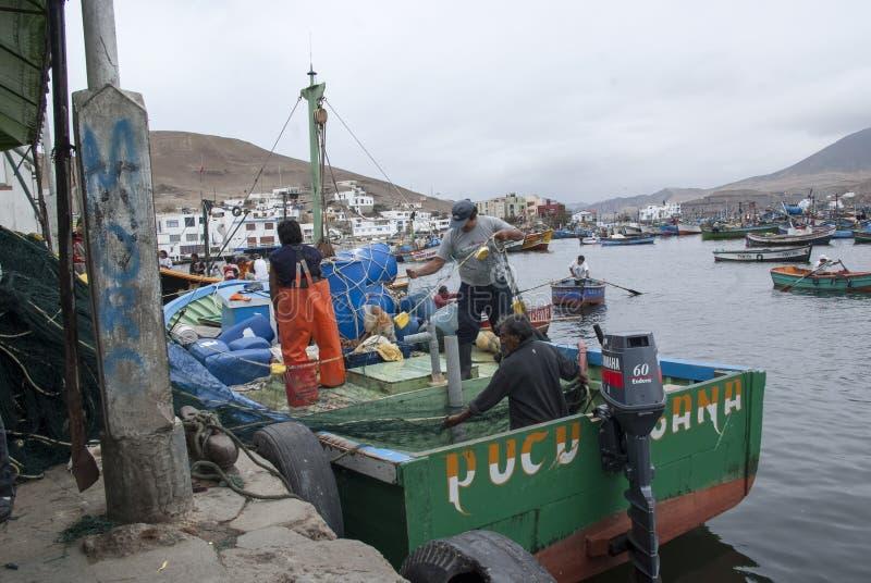 Pucusana, Pérou - 17 juin 2017 : Pêcheur péruvien dans une stalle de seiches dans le pilier de Pucusana dans un matin nuageux dan photo stock