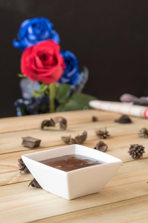 Pudín de chocolate con las fresas y el fondo de las rosas imagen de archivo