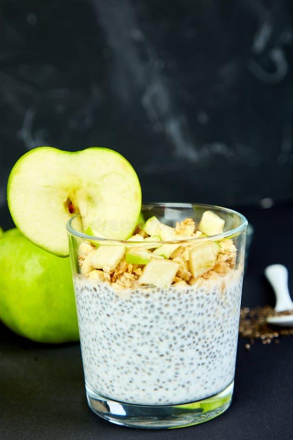 Pudín sano del chia con las manzanas y el granola en vidrio imagenes de archivo