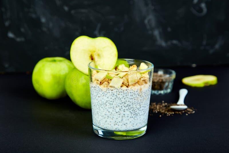 Pudín sano del chia con las manzanas y el granola en vidrio fotografía de archivo