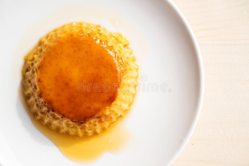 Pudding fait maison de crème anglaise du plat blanc Au-dessus de la table en bois photographie stock libre de droits