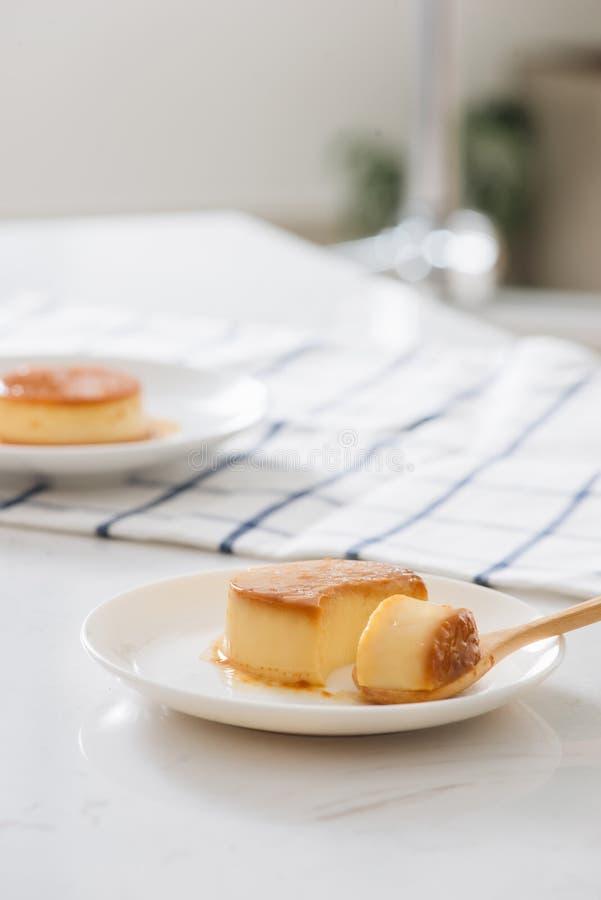 Pudding fait maison de cr?me anglaise de caramel de coupe de la main de la femme du plat blanc Au-dessus de la table blanche avec photographie stock