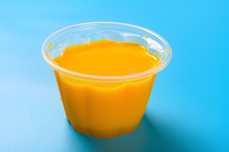 Pudding fait maison de saveur de mangue sur le fond bleu images stock