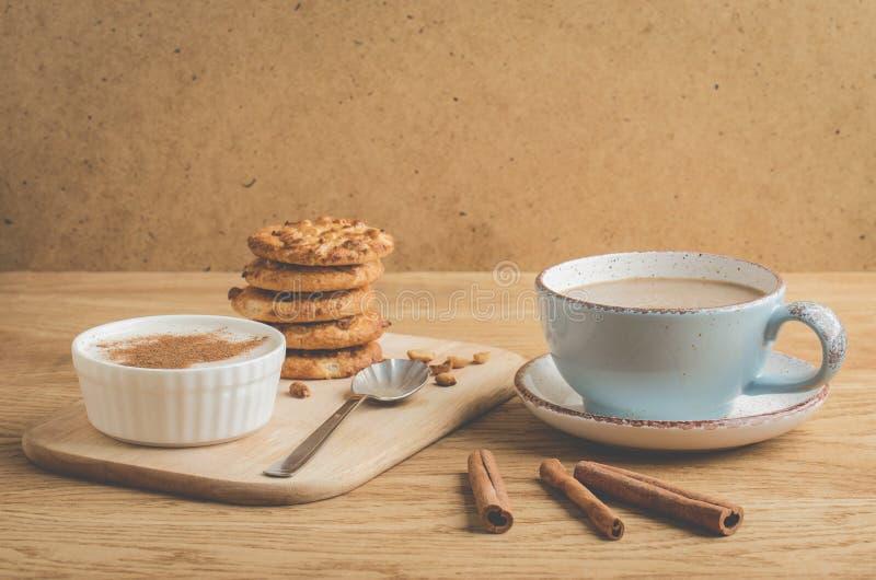 pudding med kanel, kakor och en kopp kaffe /pudding med kanel, kakor och en kopp kaffe på en trätabell arkivfoto