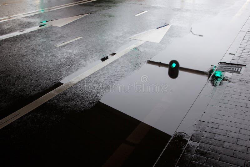 Puddle на влажной улице и отражении светофоров стоковое изображение