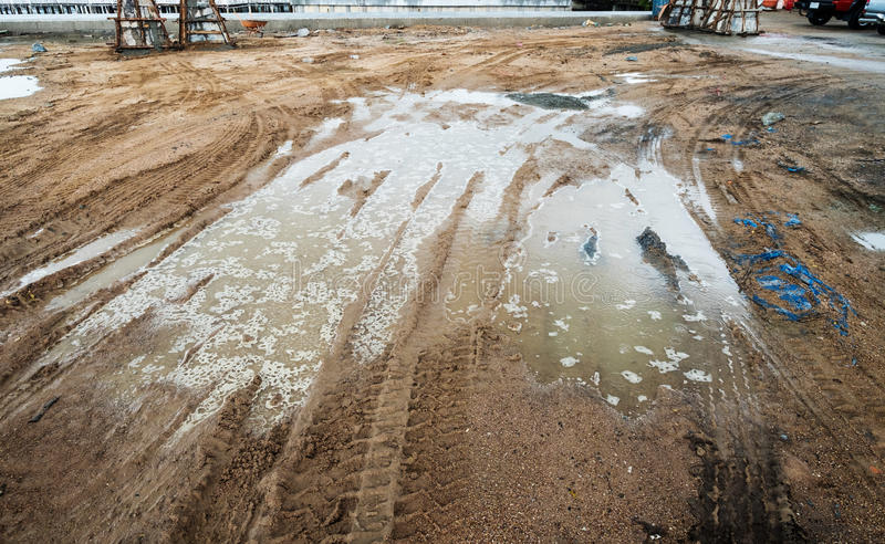 Puddle and mud with truck wheel track at construction site in rainy day royalty free stock photos