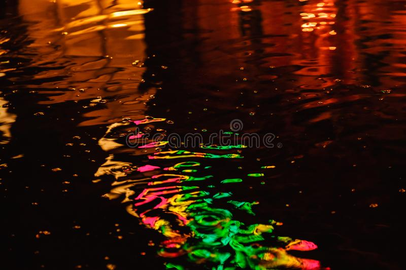 A puddle on a rainy night in the city with reflections of lanterns and advertising sign in multicolor tones royalty free stock images