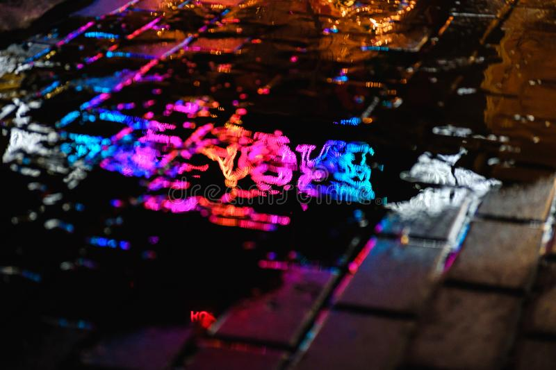 A puddle on a rainy night in the city with reflections of lanterns and advertising sign in blue tones royalty free stock photography