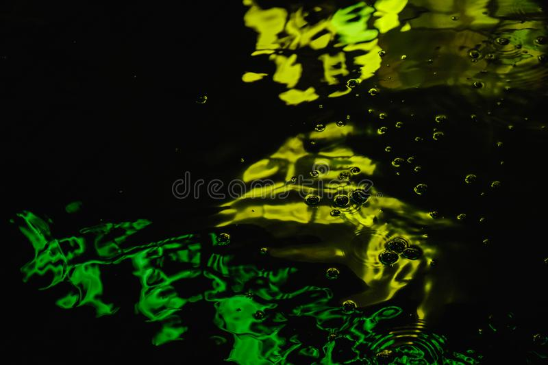 A puddle on a rainy night in the city with reflections of lanterns and advertising sign in green tones stock photos