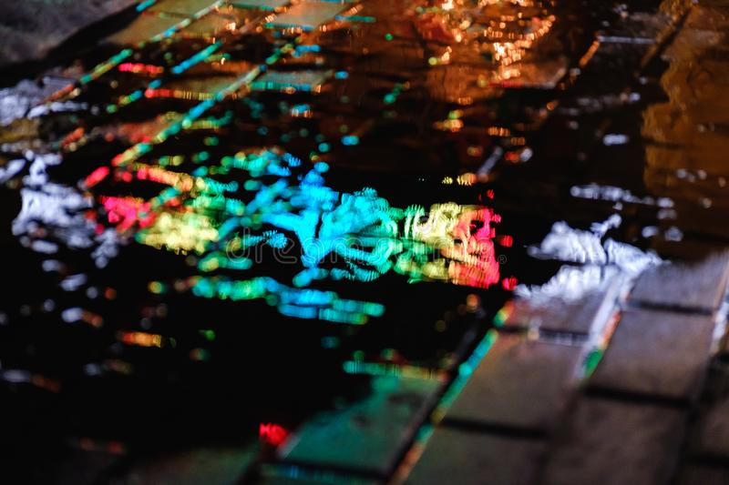 A puddle on a rainy night in the city with reflections of lanterns and advertising sign in blue tones royalty free stock image