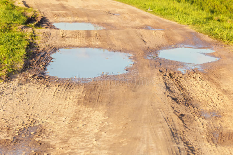 Puddles on dirt road. Big puddles on dirt road at summer day stock photography
