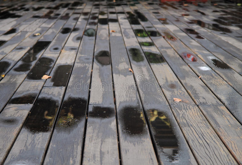 Puddles after rain on wooden planks stock photos