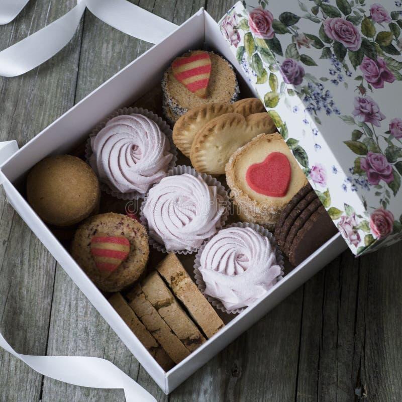 Pudełko cukierki: ciastka, marshmallow, beza w pudełku na stole, ciastka w formie serca romantyczny prezent dla zdjęcie royalty free