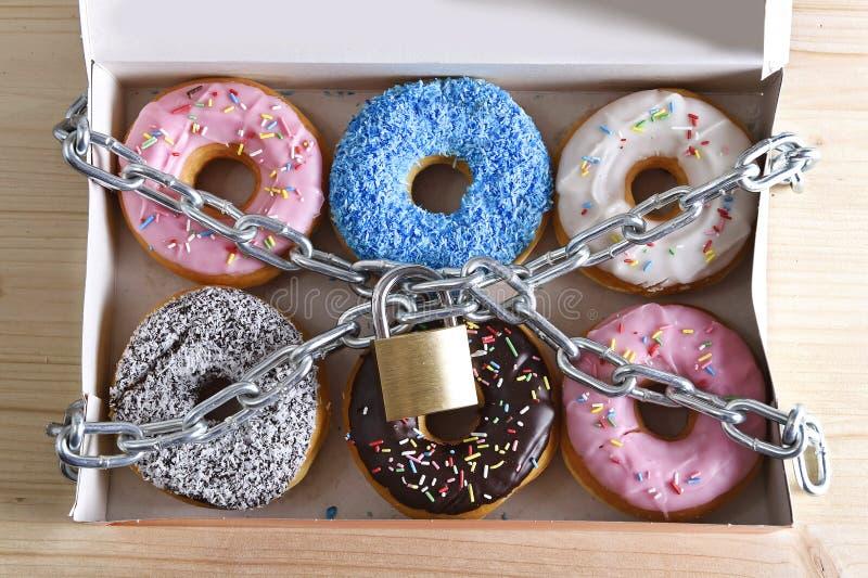 Pudełko pełno kusić wyśmienicie donuts zawijających w metalu kędziorku w nałogu i łańcuchu cukrowym i słodkim fotografia stock
