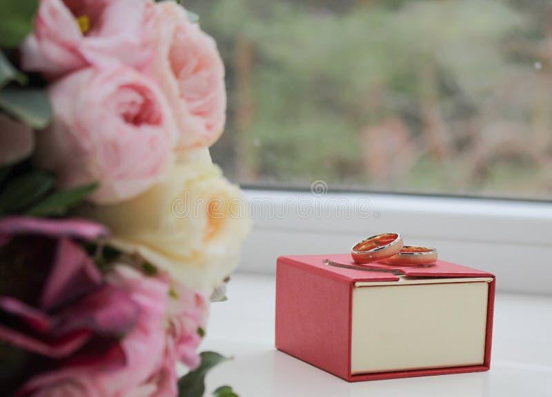 Pudełko z obrączkami ślubnymi i bukietem obrazy stock