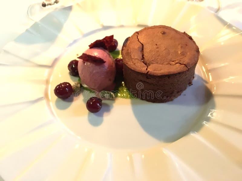 Pudim de chocolate quente delicioso com gelado vermelho de frutos de baga imagem de stock royalty free