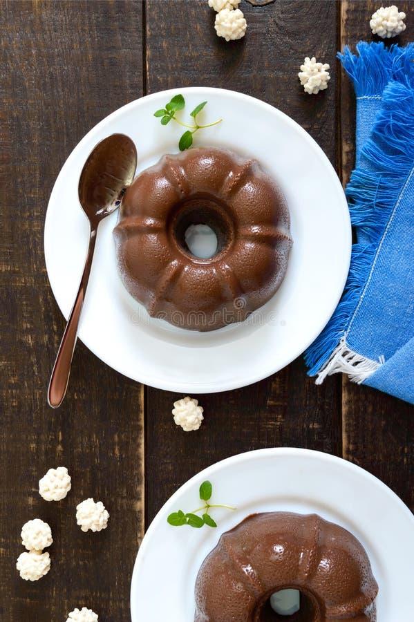 Pudim de chocolate saboroso nas placas brancas em um fundo de madeira escuro Sobremesa clara de baixo-caloria para o café da manh imagens de stock