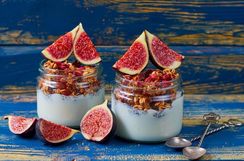 Pudim do leite de Chia com granola e os figos cortados frescos nos frascos de vidro na mesa de cozinha de madeira azul Café da ma imagem de stock royalty free