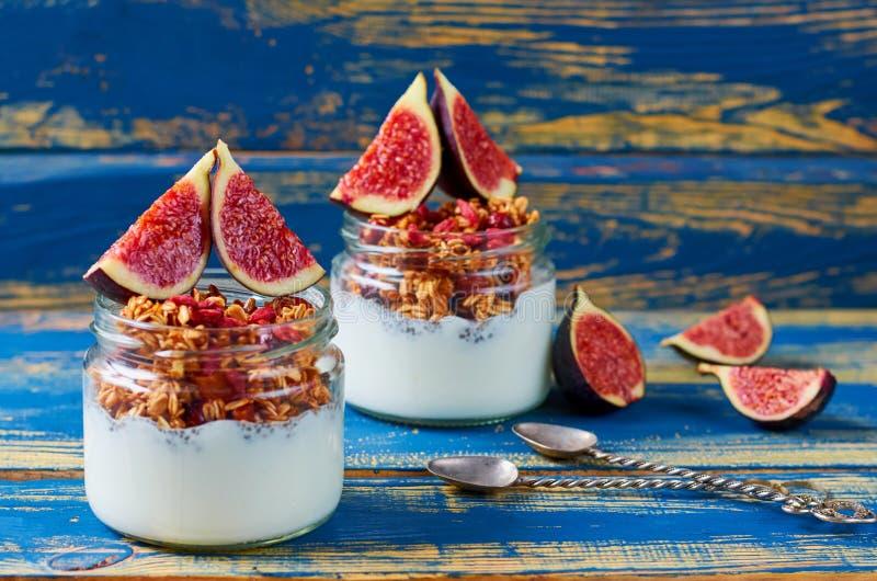Pudim do leite de Chia com granola e os figos frescos nos frascos de vidro na mesa de cozinha de madeira azul Café da manhã dos s foto de stock