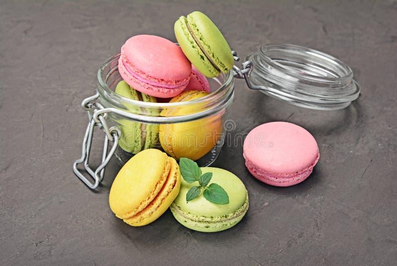 Pudim francês do fundente do chocolate Bolinhos de amêndoa ou macarons coloridos doces com a hortelã no frasco de vidro imagens de stock royalty free