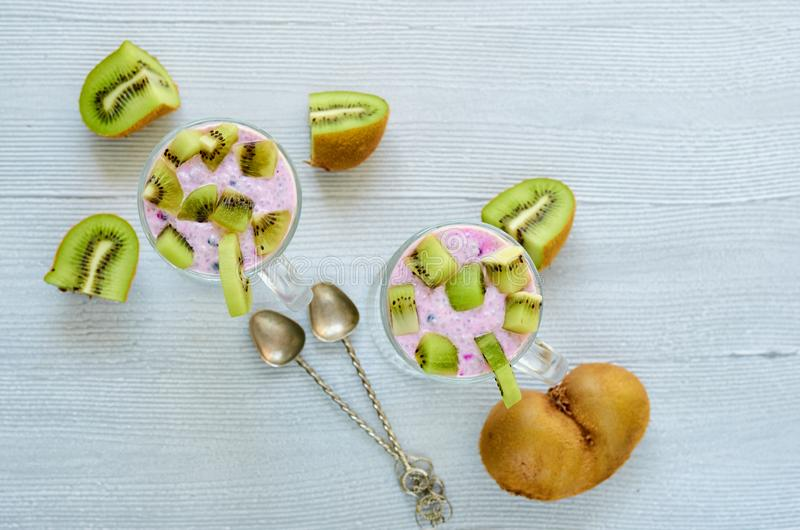 Pudim saudável do mirtilo do chia em dois vidros com iogurte e fruto de quivi cortado fresco Café da manhã dos superfoods da desi imagens de stock royalty free