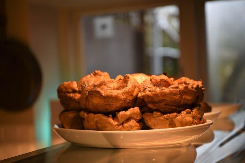 Pudins de Yorkshire dourados deliciosos para um jantar do assado imagens de stock